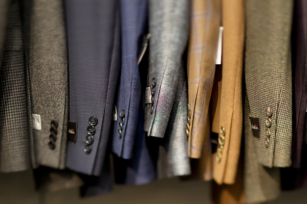 Close-up of suits hanging in store.